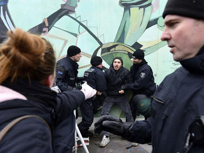Police arrest an activist during a protest against the removal of a section of the East Side Gallery, a 1,3 km long remainder of the Berlin Wall. Since 1990, the outdoor gallery has been covered in brightly coloured graffiti murals, including the famous