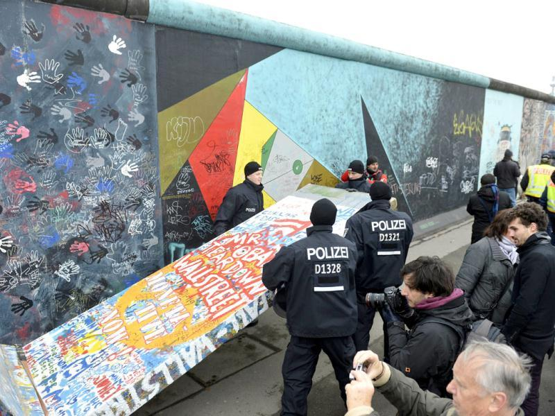 Police remove a piece of fake concrete used by protesters to fill out a hole during the removal of a section of the East Side Gallery. The 3.6-metre high (11 feet) stretch is a tourist magnet and a must-see for history buffs retracing the dark chapter of Berlin's 28-year-long division who are otherwise hard pressed to find remnants of the Wall to photograph. AFP/Odd Andersen
