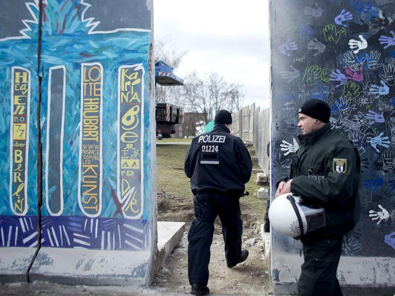 German police officers protect a part of the former Berlin Wall in Berlin. Another small section of the East Side Gallery was removed a few years ago in conjunction with the building of a new sports and concert arena. AP/Markus Schreiber