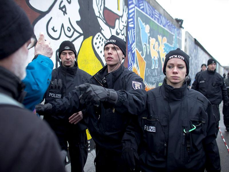 A German police officer reacts to protestors as they protect a part of the former Berlin Wall in Berlin. Crews were only able to remove one approximately 1.5 meter (yard) section from a mural depicting a stylized version of another Berlin landmark, the Brandenburg Gate, before the protests stopped the work. AP/Markus Schreiber/Pool