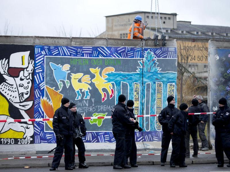 German police officers protect a part of the former Berlin Wall and a construction worker who fixed a part of the wall at a crane in Berlin. The respite is likely only temporary, however, despite calls to halt the construction permanently. AP/Markus Schreiber