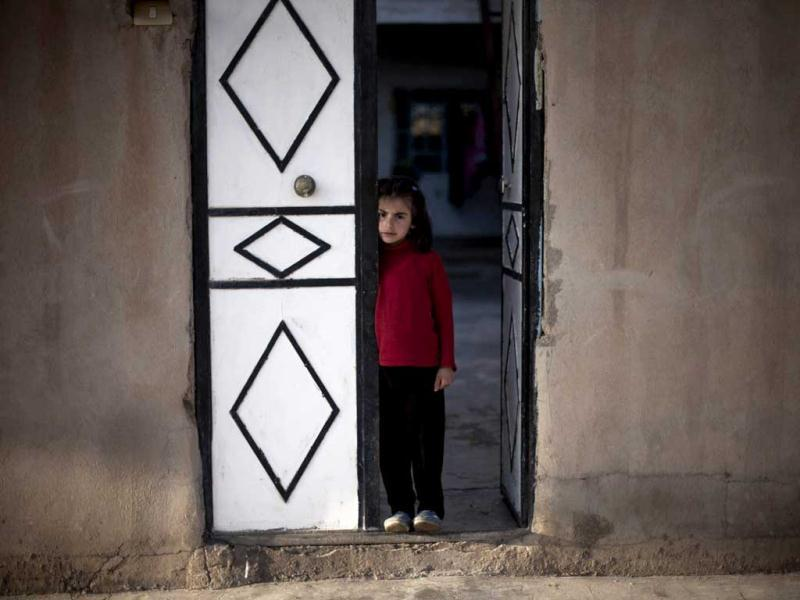 A Kurdish girl stands at the door of her house in the town of Qamishli, a Syrian Kurdish area. AP Photo