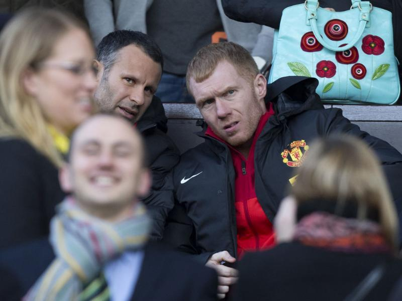 Manchester United's Ryan Giggs takes his seat in the stands alongside teammate Paul Scholes before their team's English Premier League soccer match against Norwich City at Old Trafford Stadium, Manchester, England. AP/Jon Super