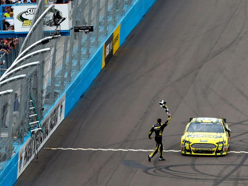 Carl Edwards, driver of the #99 Subway Ford, celebrates with the checkered flag after winning the NASCAR Sprint Cup Series Subway Fresh Fit 500 at Phoenix International Raceway in Avondale, Arizona. (AFP Photo)