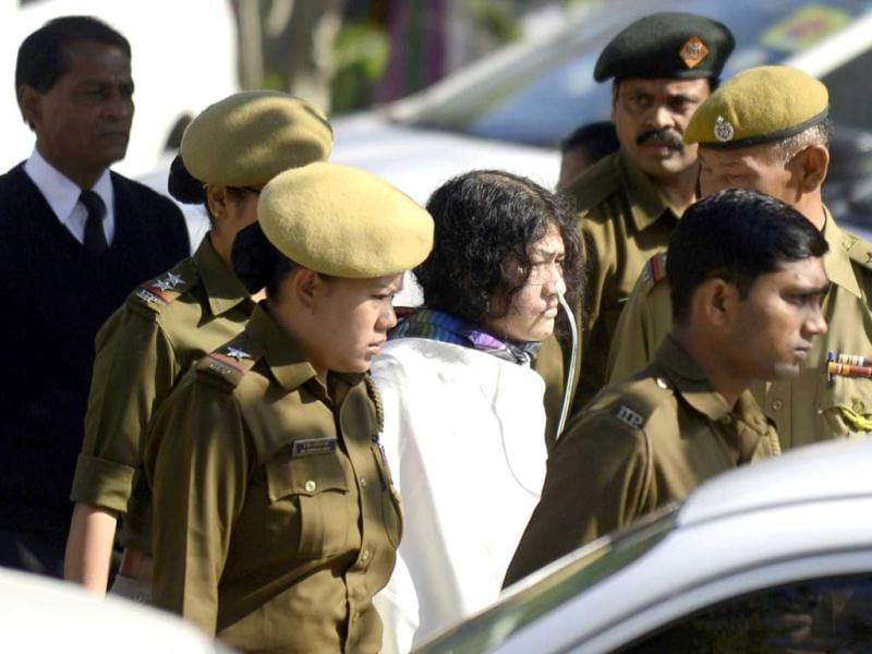 Anti-AFSPA activist Irom Sharmila (C, in white) walks with security personnel as she arrives for an appearance at Patiala court in New Delhi. AFP PHOTO