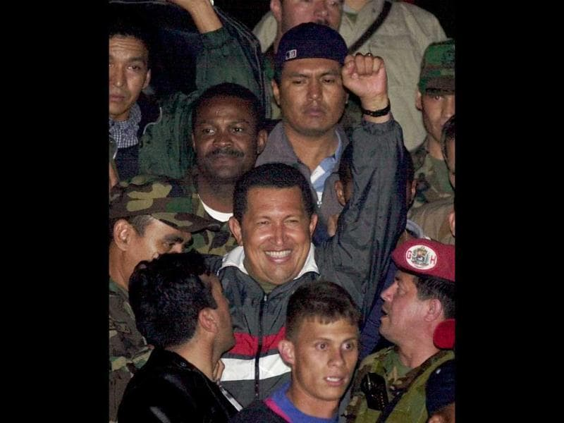Venezuela's President Hugo Chavez gestures to supporters as he arrives to Miraflores presidential palace after being freed by his military captors two days after the military announced he had resigned in Caracas, Venezuela. (AP)