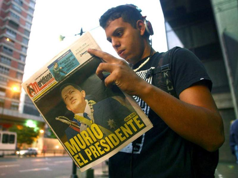 A youngster reads a local newspaper the day after the death of Venezuelan President Hugo Chavez in Caracas. AFP photo