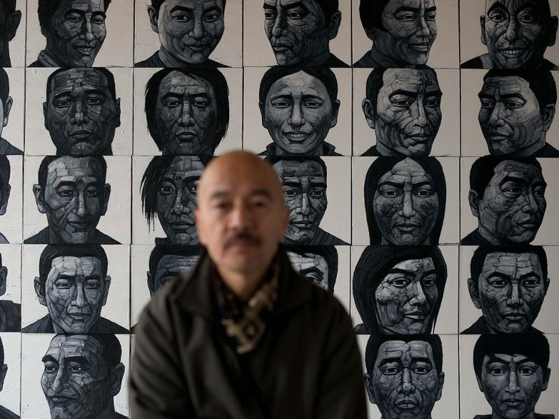 Artist Liu Yi arranges paintings showing the faces of Tibetan self-immolators at his studio on the outskirts of Beijing. (AFP)