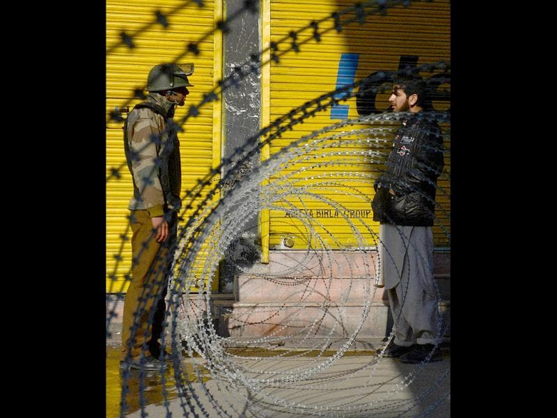 A policeman questions a Kashmiri Muslim behind a barbed fence during a curfew in Srinagar. (AFP)