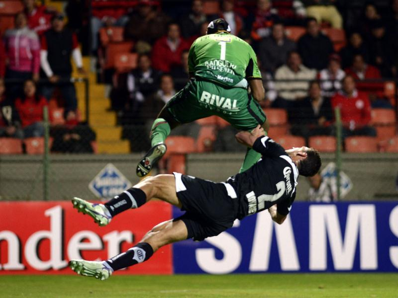 Maximo Banguera (L) goalkeeper of Barcelona of Ecuador vies for the ball with Diego Novaretti (L) of Toluca of Mexico during their Libertadores Cup football match at the Nemesio Diez Stadium in Toluca, Mexico. (AFP)