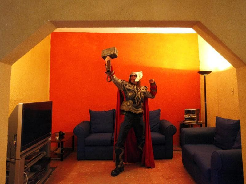 Street artist Ruben Oviedo, dressed as comics superhero Thor, poses for a portrait in the living room of his home in Mexico City. (Reuters)