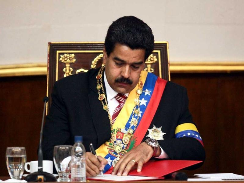 Venezuelan acting president Nicolas Maduro signing a document after being sworn in by the President of the National Assembly, Diosdado Cabello (out of frame), during a ceremony in Caracas. AFP photo