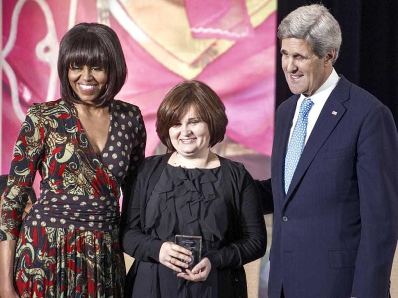 US First Lady Michelle Obama (L) and US Secretary of State John Kerry (R) stand for a photos with Elena Milashina (C) of Russia after presenting her with the Secretary of State's International Women of Courage Award inside the Dean Acheson Auditorium of the US Department of State in Washington. AFP photo