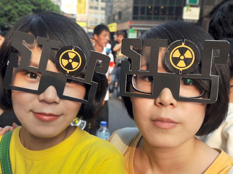 Twin protesters wear protest glasses during an anti-nuclear demonstration in front of the presidential office in Taipei. AFP/Mandy Cheng