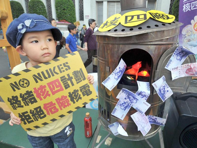 A girl holds a poster during an anti-nuclear demonstration in front of the Central Bank in Taipei. Tens of thousands of Taiwanese people rallied in the capital to demand the government heed the lesson of a Japanese atomic crisis and scrap the island's nuclear facilities, organisers said. AFP/Mandy Cheng