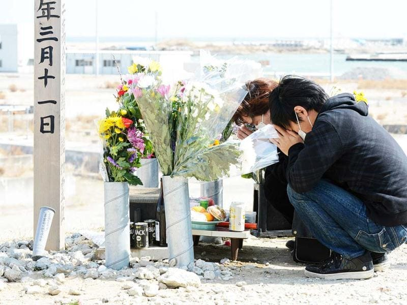 A couple prays for tsunami victims in front of an altar amid the devastated area of Yuriage district in Natori, Miyagi Prefecture. (AFP)