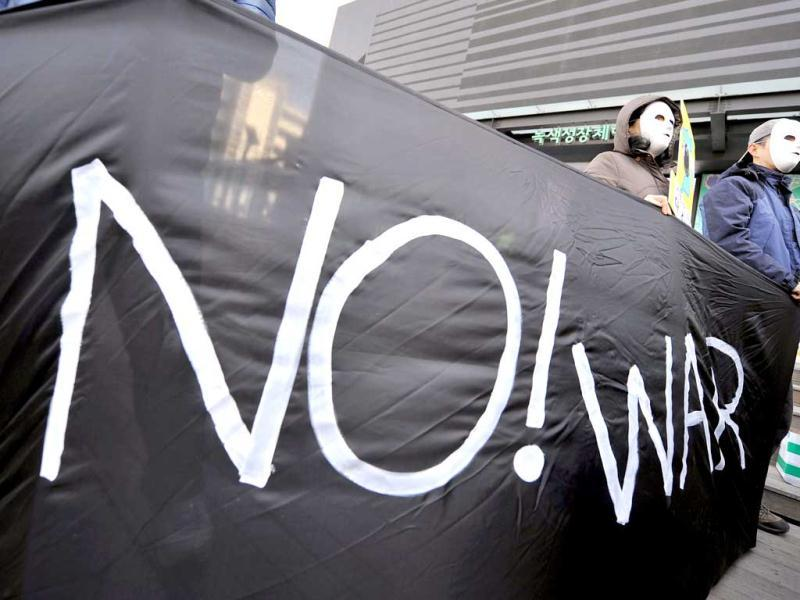 Anti-war activists wearing masks hold a black banner reading