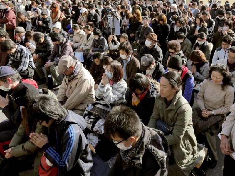 People observe a moment of silence for the victims of the March 11, 2011 earthquake and tsunami during an event at a park in Tokyo. AP Photo