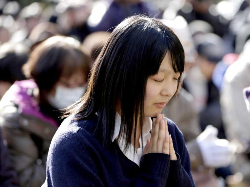 A woman takes part in a moment of silence as they rememeber the Tsunami disaster in Tokyo.Reuters photo