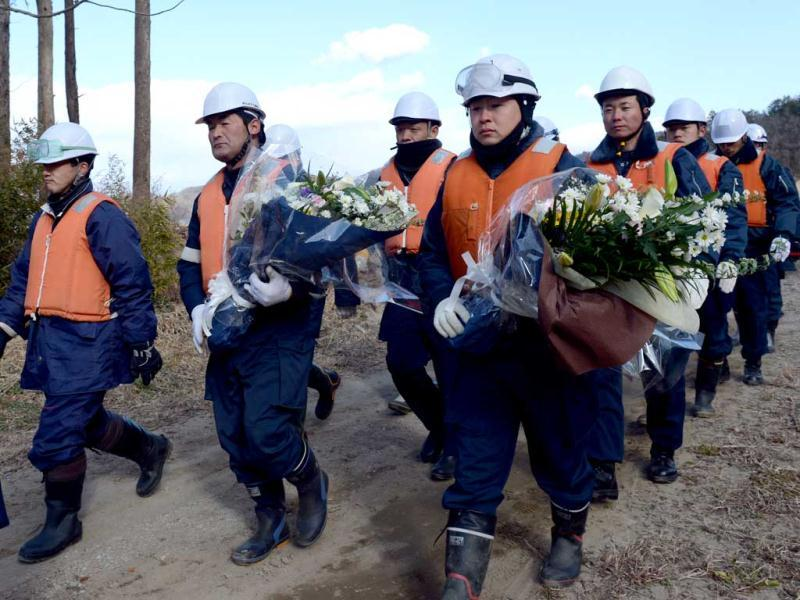 Police officers carry bouquets of flowers as they return to recommence their search misson for tsunami victims at the mud-covered riverside field near the Okawa elementary school in Ishinomaki city, Miyagi prefecture.AFP Photo