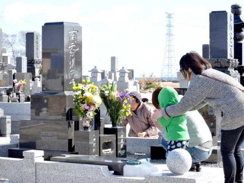 A family prays for their relatives killed by the 2011 tsunami at a cemetery in Minamisoma in Fukushima prefecture. AFP Photo