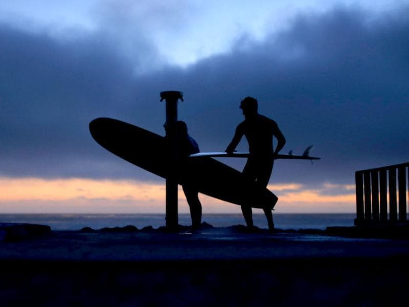 Surfers shower off on the beach after paddling to shore long after sunset in Cardiff, California. Reuters photo