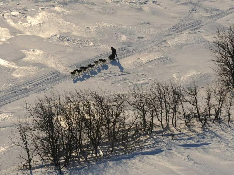A musher kicks while traveling to Koyuk in Alaska during the Iditarod Trail Sled Dog Race. AP photo/Bill Roth