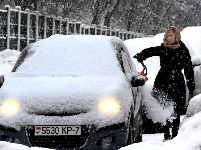 A woman removes snow from her car in the Belarus capital Minsk. (AFP)