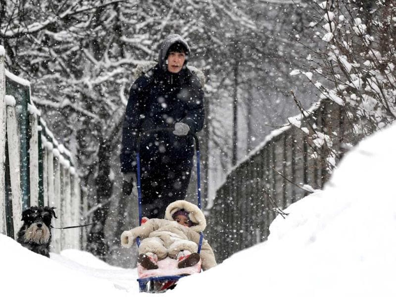 A woman walks with a child and dog in a snow covered park in the Belarus capital Minsk. (AFP)