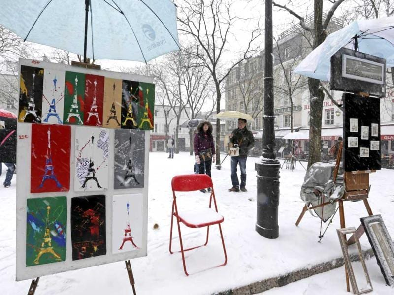 Paintings are displayed on the snow-covered 'Place du Tertre', a square at the Butte Montmartre area near the Sacre Coeur basilica in Paris as winter weather with snow and freezing temperatures returns to northern France. (Reuters)