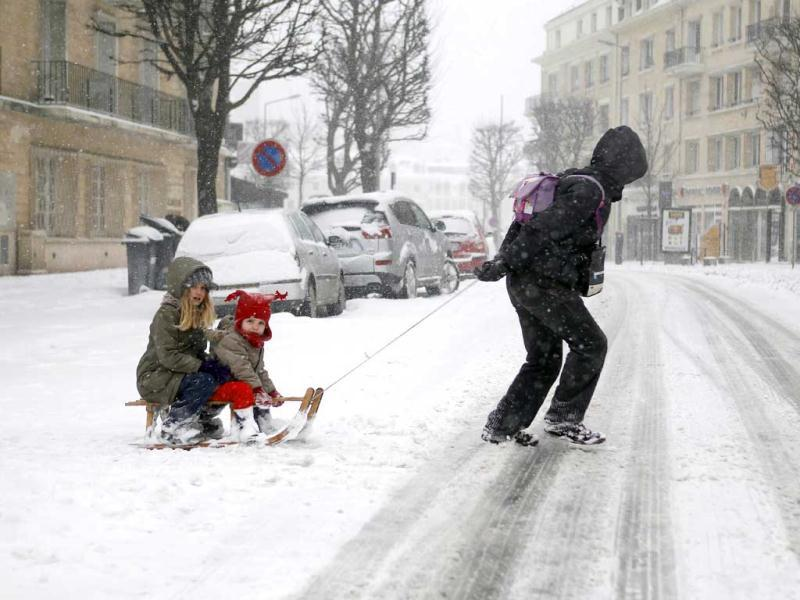 Children cross a snowy road on a sledge, in Caen, northwestern France, during a heavy snow storm on France. (AFP)