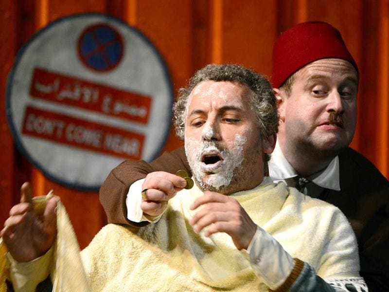 French actor Atmen Kelif (L), playing the Ali Baba character, performs with fellow actor Thomas Morris, playing Qassim, during the general of Ali Baba at the Theatre de la Criee in Marseille. (AFP)
