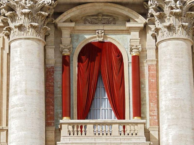 The red curtain on the central balcony, called the Loggia of the Blessings of Saint Peter's Basilica, where the new pope will appear after being elected in the conclave is seen at the Vatican. Once cast, the ballots are opened one by one by three different