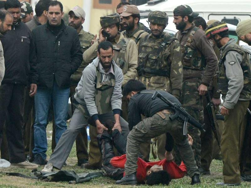 Policemen move the body of an alleged militant following the attack. AFP/Tauseef Mustafa