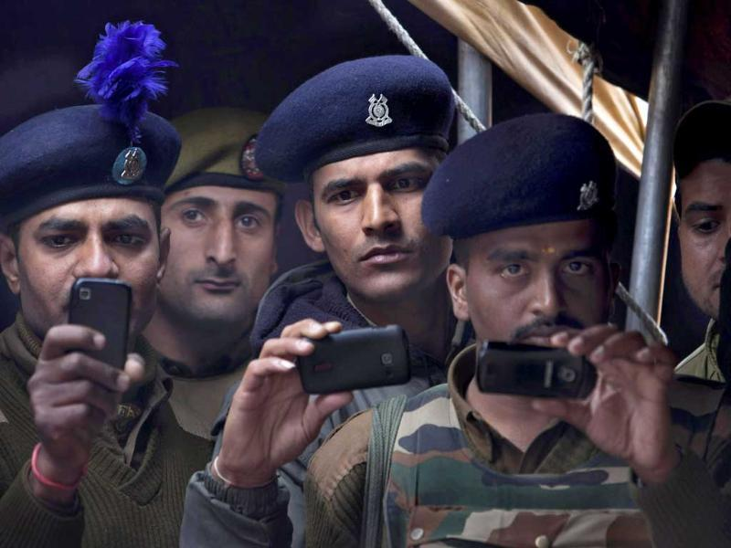 CRPF soldiers and police officers take pictures with their cell phones during wreath laying ceremony of their colleagues at the police headquarters in Srinagar. AP Photo
