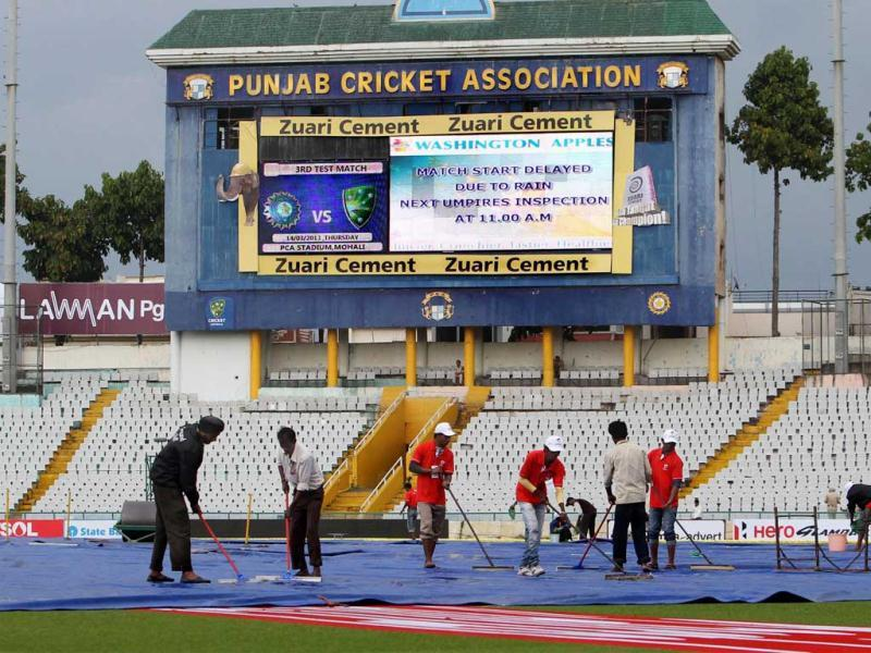 Groundmen clear the pitch for the 3rd Test as rain delayed the start of the match at PCA Stadium in Mohali. (PTI)