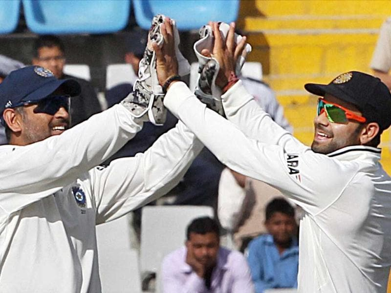 MS Dhoni and Virat Kohli celebrate after taking the wicket of Australian player ED Cowan during the second day of the 3rd Test match at PCA Stadium in Mohali. (PTI)