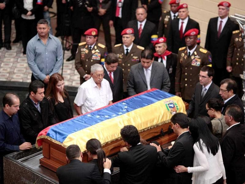 In this photo released by Miraflores Press Office, Hugo de los Reyers Chavez, the father of Venezuela's late President Hugo Chavez, center in white shirt, stands by his son's coffin at the military museum in Caracas, Venezuela. (AP Photo)