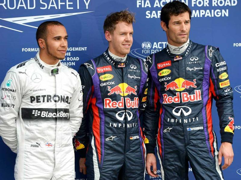 Red Bull driver Sebastian Vettel of Germany (C) poses for the photographers after qualifying in pole position ahead of teammate Mark Webber of Australia (R) and third fastest, Mercedes driver Lewis Hamilton of Britain (L) during the qualifying session for the Formula One Australian Grand Prix at the Albert Park circuit in Melbourne. (AFP Photo)