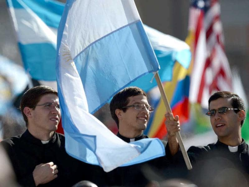 Priests wave an Argentinian flag during the inauguration mass of Pope Francis at St Peter's square at the Vatican. AFP Photo