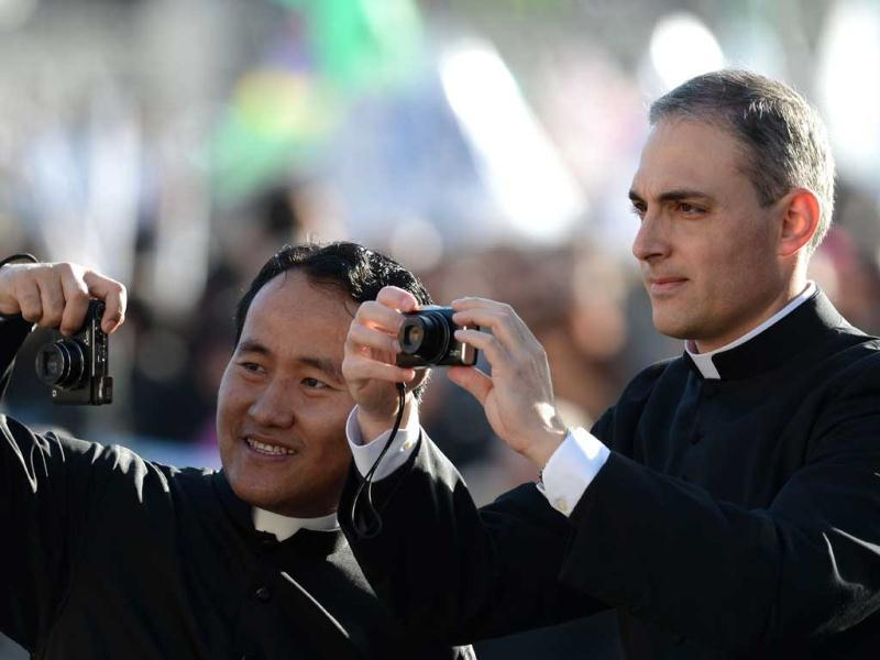 Priest take pictures in St Peter's square before the inauguration mass of Pope Francis at the Vatican. AFP Photo