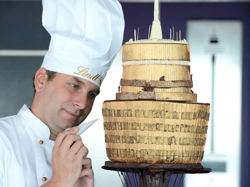 Thomas Schnetzler puts the finishing touches to a chocolate replica of the iconic Sydney Tower on the observation deck of the tower. AFP/Greg Wood