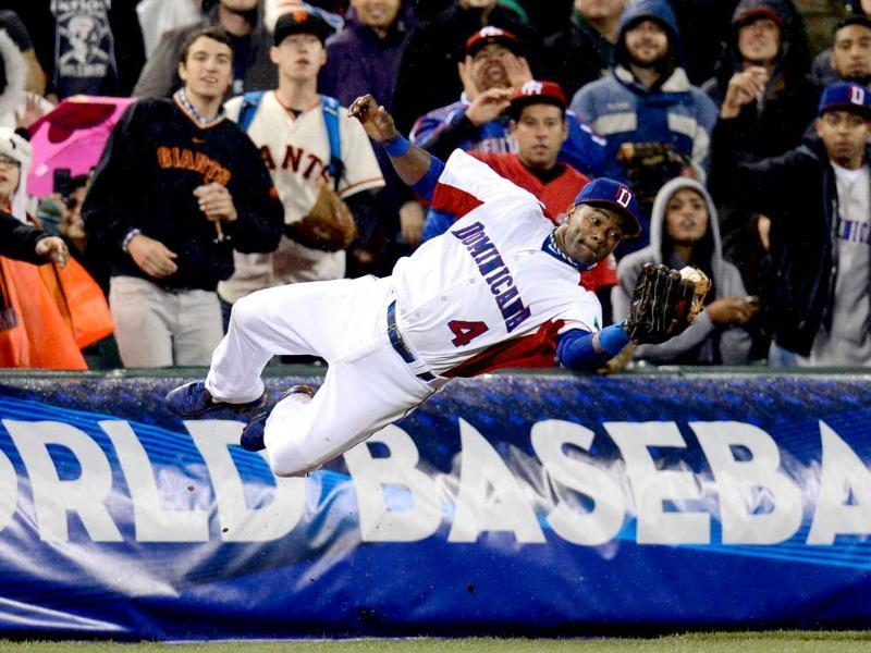 Miguel Tejada of the Dominican Republic dives to make a catch in foul territory as Moises Sierra look on against Puerto Rico during the Championship Round of the 2013 World Baseball Classic in San Francisco, California. AFP/Thearon W Henderson/Getty Images