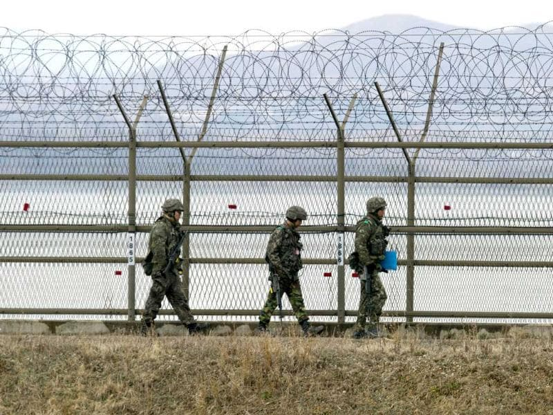 South Korean soldiers patrol along an iron fence fortified with barbed wire near the Demilitarized Zone (DMZ) dividing the two Koreas in the border city of Paju. AFP/Jung Yeon-Je