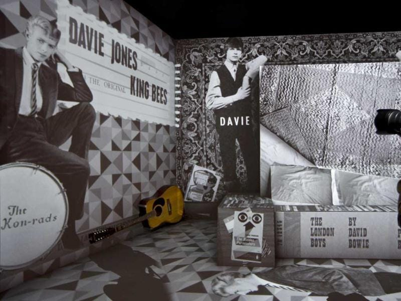A photographer is seen taking pictures of a retrospective David Bowie exhibition, entitled David Bowie Is, depicting Bowie's move from Surburbia to Soho, along with his Harptone acoustic guitar, at the V&A Museum in west London. (AP Photo)