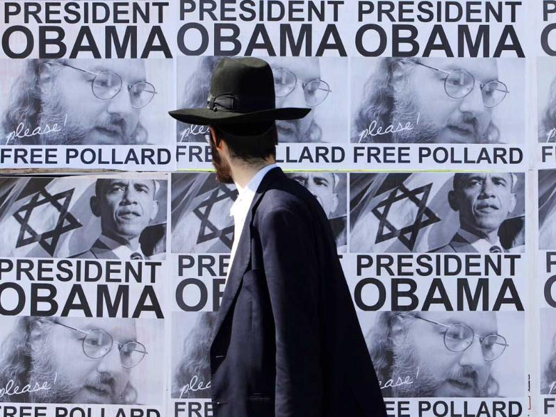 An ultra-orthodox Jewish man walks past posters calling for US President Barack Obama to free Jonathan Pollard from a US prison, in Jerusalem. Reuters
