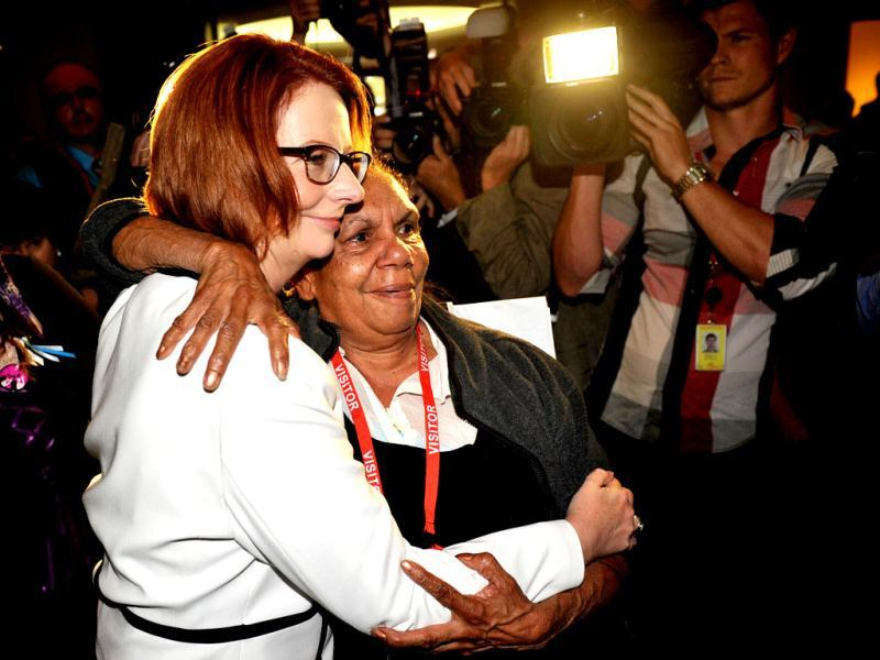 Australia's Prime Minister Julia Gillard (L) is embraced by a woman during a ceremony on the National Apology for Forced Adoptions at Parliament House in Canberra. AFP