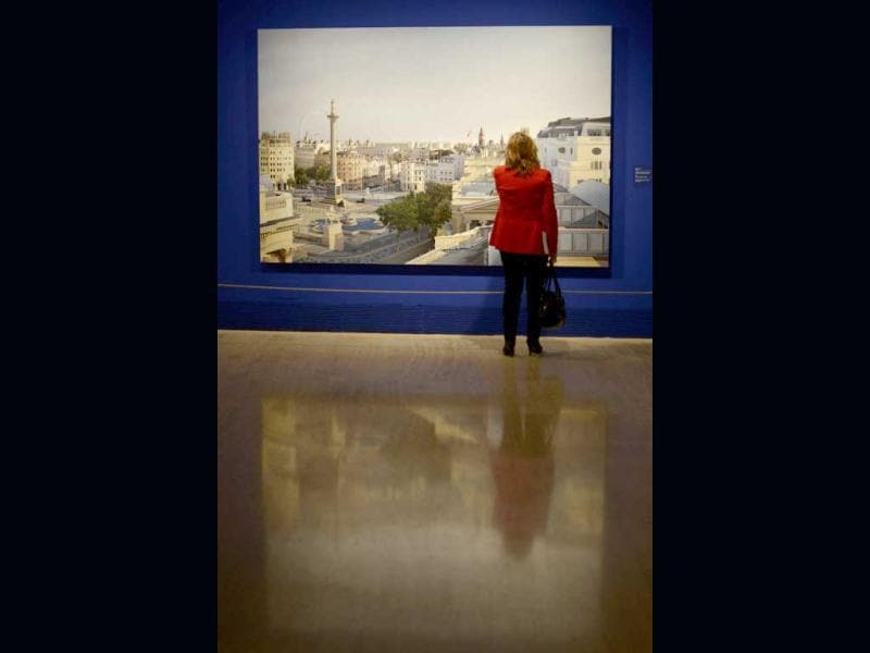 A woman stands in front of a painting by British artist Clive Head entitled 'Leaving the Underground' (2010) during the exhibition 'Hyperrealism 1967-2012' at the Thyssen-Bornemisza museum in Madrid. (AFP Photo/Pedro Armestre)