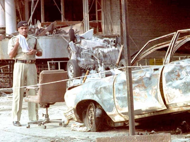 File photo of March 14, 1993: An Indian police officer stands beside a charred automobile outside the Air India Building in Mumbai, after a series of bombings. (AFP Photo)