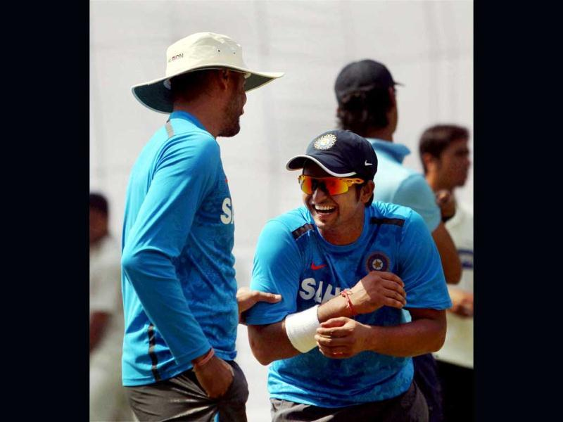 Suresh Raina sharing a light moment with Harbhajan Singh during a practice session for the 4th test match against Australia in New Delhi. PTI Photo